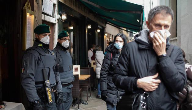 Policías y turistas, con mascarillas, en las calles de Venecia.