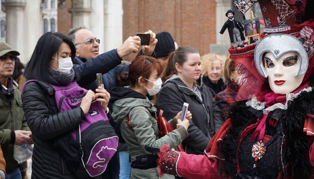 Foto de turistas con mascarillas visitando la plaza de San Marcos en Venecia por el coronavirus.