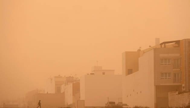 Un hombre pasea por el barrio de Majada Marical, cubierto por una densa calima procedente de África, este domingo en Puerto del Rosario (Fuerteventura).