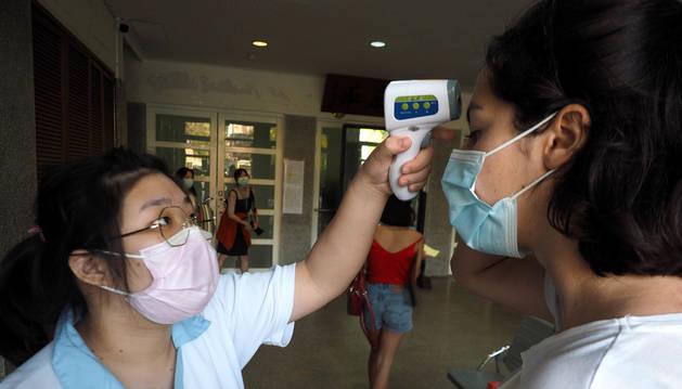 Foto de una sanitaria tomándole la temperatura a una joven en Taiwan, ante el coronavirus.