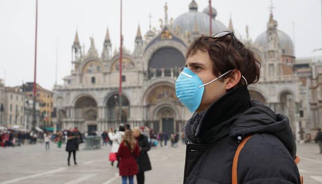 Foto de un turista, protegido con una mascarilla, en las calles de Venecia, ante el coronavirus.