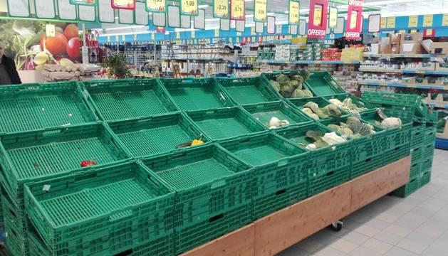 Imagen de un supermercado italiano con las cestas de la fruta y verdura totalmente vacías.