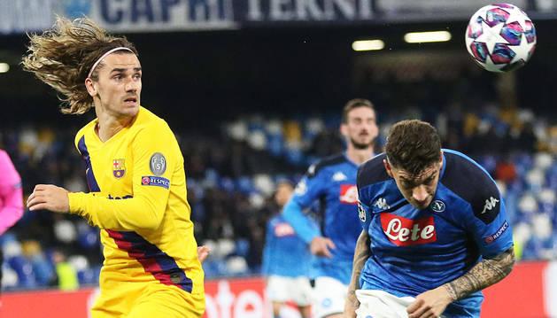 El italiano Di Lorenzo trata de despejar un balón en presencia del francés Antoine Griezmann durante el encuentro.