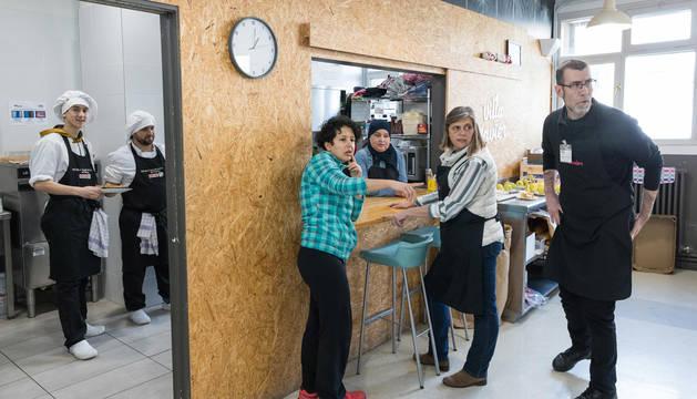 Varios voluntarios del comedor social Villa Javier Tudela se disponen a servir los platos a los usuarios.