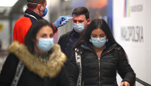 Un sanitario toma la temperatura a un joven en el aeropuerto de Cracovia.