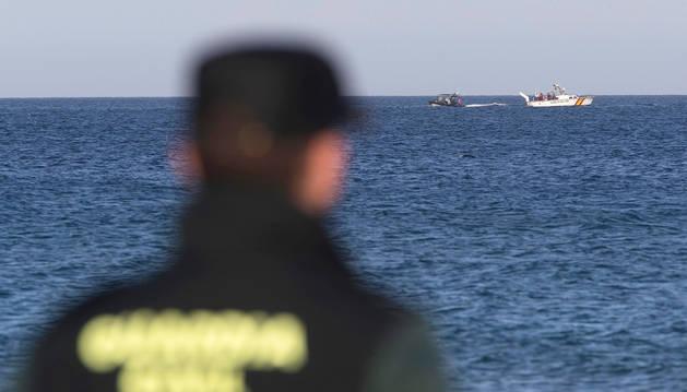 Un agente observa las embarcaciones de la Guardia Civil y del Ejército del Aire durante las labores de búsqueda del avión estrellado.