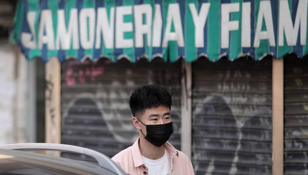 Un joven de rasgos asiáticos camina por el distrito madrileño de Usera protegiendo su rostro con mascarillas tras el anuncio de decenas de casos de pacientes con coronavirus en España.