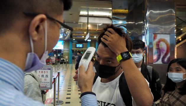 Un trabajador controla la temperatura corporal a los pasajeros en una terminal de autobús de Taipei, en Taiwan.