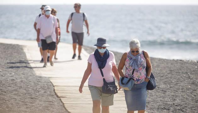 Varios turistas pasean este viernes por las inmediaciones del hotel en el que desde el pasado lunes permanecen incomunicados sus huéspedes y trabajadores al dar positivo en coronavirus cuatro de los que se alojaban en el centro turístico de Adeje, en el sur de Tenerife.