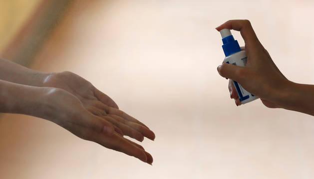 Una persona rocía con gel higienizante las manos de otra en prevención de contagios.