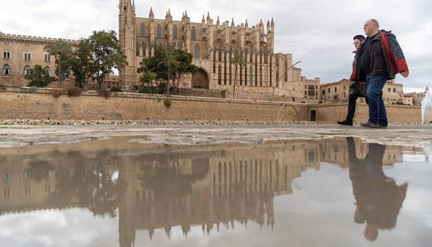 Dos viandantes pasan junto a un charco cerca de la catedral de Palma de Mallorca.