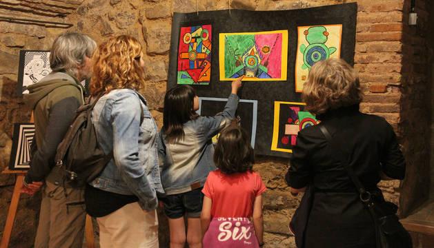 Padres y alumnos contemplan una exposición de pintura abstracta realizada por escolares.