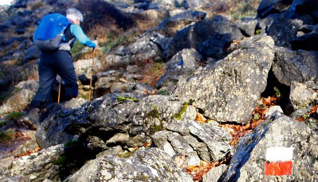 Foto de un caminante, afrontando un ascenso por un sendero GR.