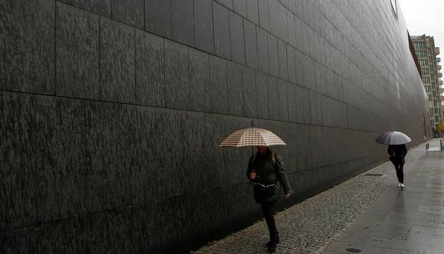 Foto de dos personas bajo la lluvia junto a Baluarte, en Pamplona.
