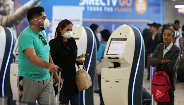 Dos pasajeros se dirigen rumbo a la puerta de embarque con mascarillas en el Aeropuerto internacional Mariscal Sucre de Quito, Ecuador.