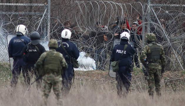foto de Un grupo de migrantes intenta de cruzar la frontera griega, mientras la policía trata de evitarlo lanzando botes de gases lacrimógenos
