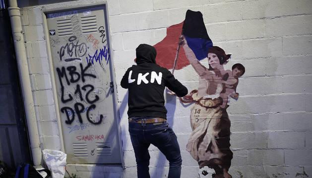El artista LKN coloca el dibujo en homenaje a Maider Irisarri, anoche en la calle Nueva junto a la plaza San Francisco de Pamplona.