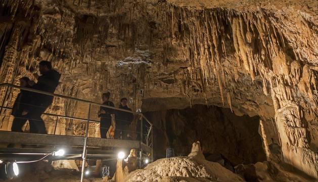Foto de un grupo de personas camina por una de las pasarelas instaladas en la cueva de Mendukilo, en Astitz.