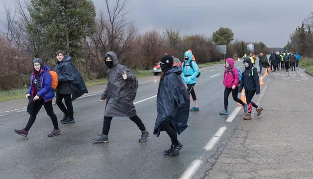 Foto de un grupo de peregrinos se protege con chubasqueros de la lluvia en la recta de Arguedas.