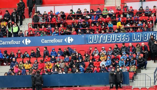 Foto de niños de las escuelas de fútbol de Fundación Osasuna presenciando el entrenamiento de Osasuna en El Sadar el 7 de marzo.