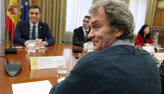 El ministro de Sanidad, Salvador Illa (i), el presidente del Gobierno, Pedro Sánchez (d), y el director del Centro de Coordinación y Alertas Sanitarias del Ministerio de Sanidad, Fernando Simón (de espaldas), durante la reunión de este lunes para el seguimiento del coronavirus en España.