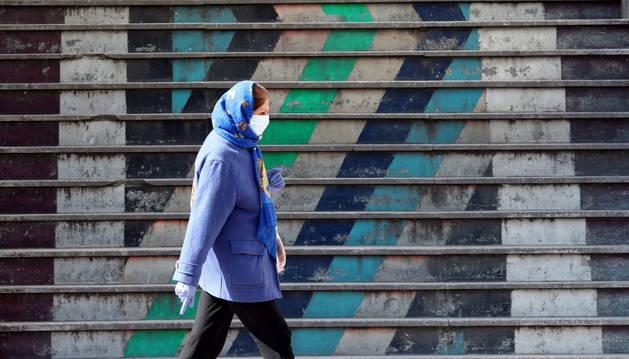 Foto de una mujer iraní con mascarilla y guantes protectores camina en una calle de Teherán, Irán.