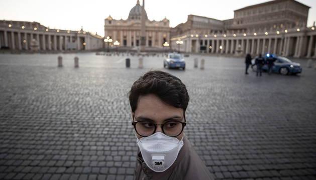 Foto de un ciudadano con mascarilla, frente a la plaza de San Pedro vacía.