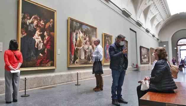 Foto de dos personas con mascarillas en la Galería Central del Prado.