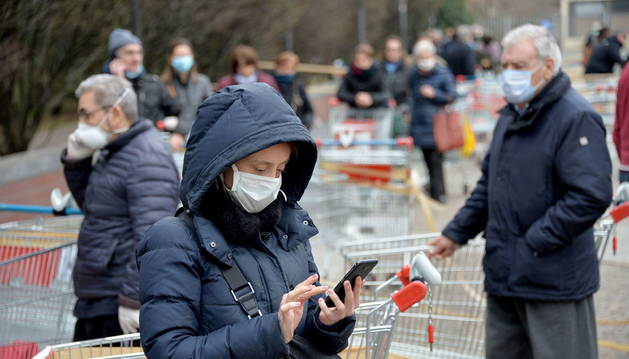 Personas con máscara hace cola en una supermercado en Italia.