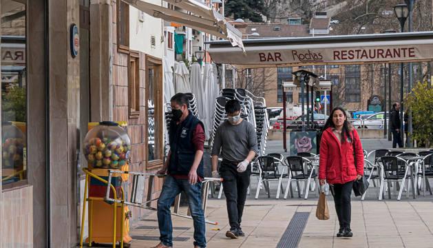 Foto de terrazas cerradas en el centro de Estella y vecinos con mascarillas para protegerse del Covid-19.