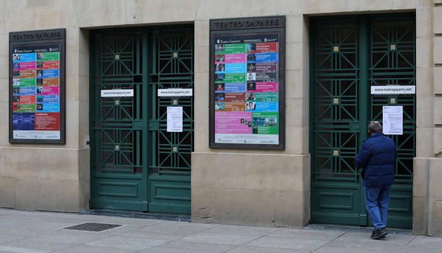 Foto de un hombre leyendo este viernes el aviso colocado en las puertas del Teatro Gayarre. Permanecerá cerrado, en principio, hasta el próximo día 27.