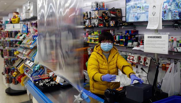 La empleada de un bazar chino de Pamplona, con protecciones ayer por la tarde junto a la caja.