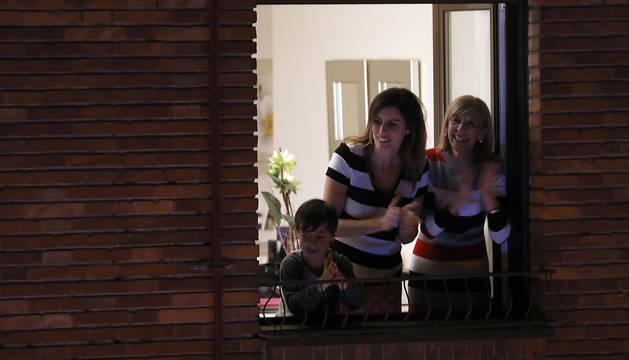 Foto de varias personas, asomadas a la ventana aplaudiendo, este sábado por la noche.