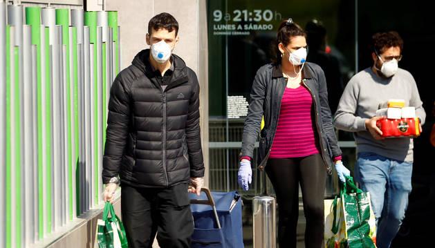 Varias persona con mascarilla a la salida de un supermercado en Madrid.