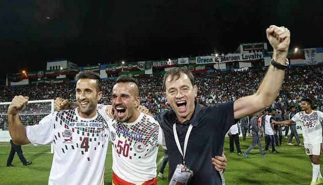 Foto de Kibu Vicuña, a la dcha, celebrando el título en un estadio Kalyani repleto, junto a sus jugadores Fran Morante (izda.) y Fran González.