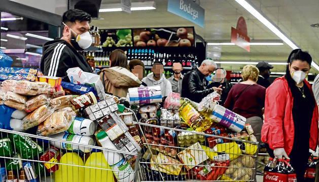 Foto de colas para hacer la compra en un supermercado.
