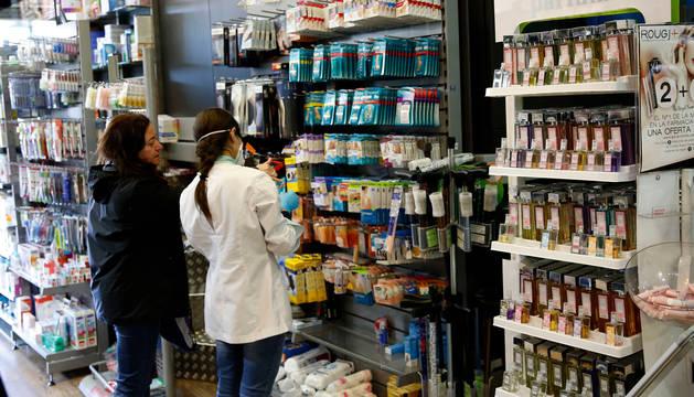 Foto de una farmacéutica acompañando a una clienta en el establecimiento de Yanguas y Miranda.