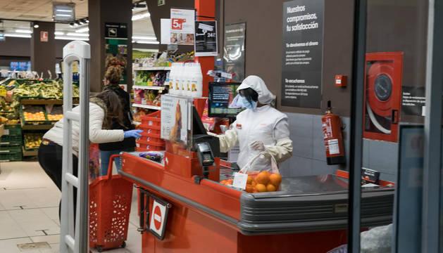 Imagen de un supermercado Eroski. La dependienta, con mascarilla, y la clienta, con guantes.