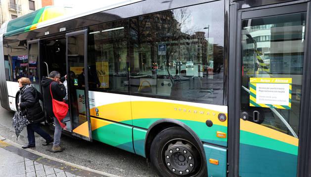 Una usuaria se apea de un autobús en Merindades mientras otro accede por la puerta central.