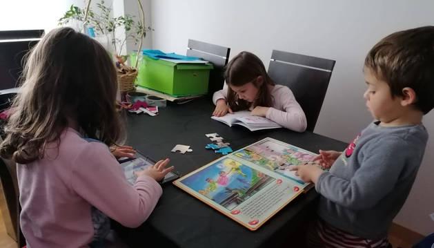 Foto de Nagore (5), Ánder (3) y Olaia (7) González Soto, tres alumnos del Colegio Público San  Miguel, este lunes a mediodía en su salón de Noáin.