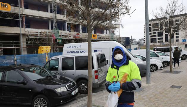Un trabajador se protege con una mascarilla en una calle de Lezkairu con un edificio en construcción.