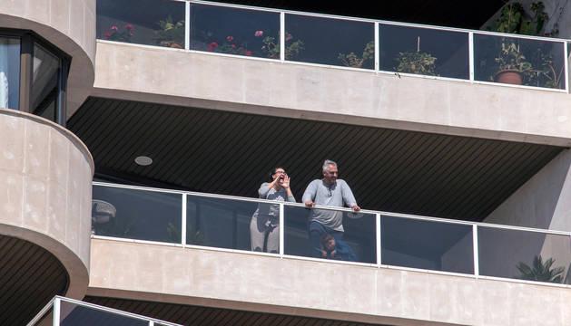 Una familia sale al balcón para tomar aire.