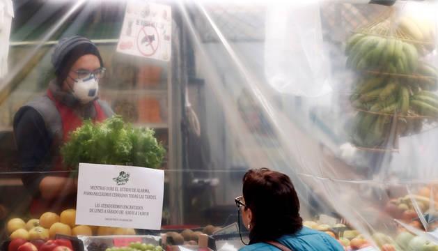 Aspecto que presentaba este miércoles uno de los puestos del mercado del Casco Viejo de Pamplona, completamente cubierto con plástico para proteger el producto y aislarlo del posible contacto exterior.