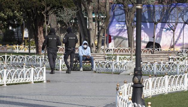 Foto de un hombre con mascarilla se sienta mientras la policía antidisturbios turca patrulla en calles vacías.