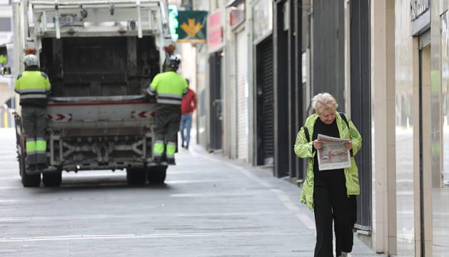 Una mujer regresa de comprar el pan y la prensa en Pamplona. Al fondo, el servicio de recogida de basuras, que sigue funcionando.