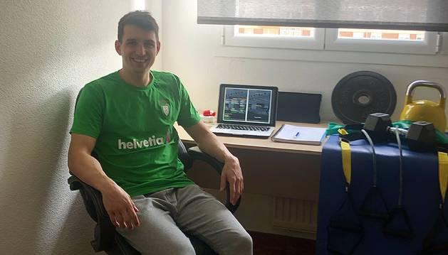 Carlos Chocarro, en su casa junto al ordenador en el que trabaja y el material que usa para entrenar.