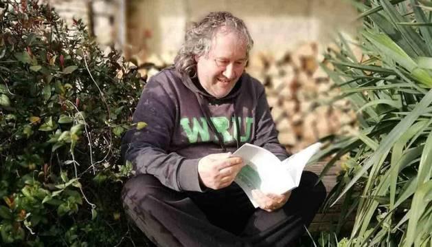 Alfredo Uriz lee un libro en el jardín de su casa familiar en Ororbia.