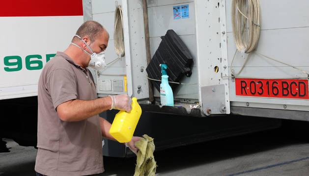 Foto de un transportista vierte lejía en una bayeta  para desinfectar su vehículo, aparcado en la Ciudad del Transporte, en Imárcoain.