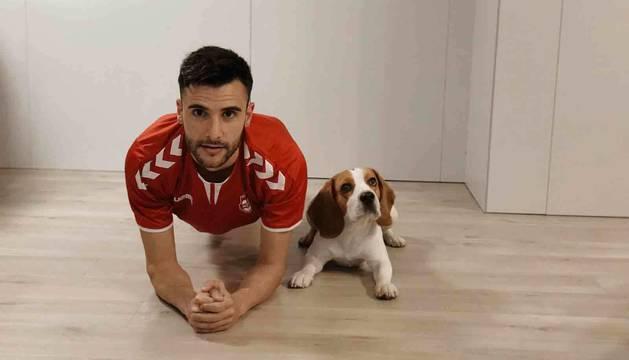 El portero de Osasuna Magna, Asier Llamas, hace una plancha en compañía de su perro Charlie.