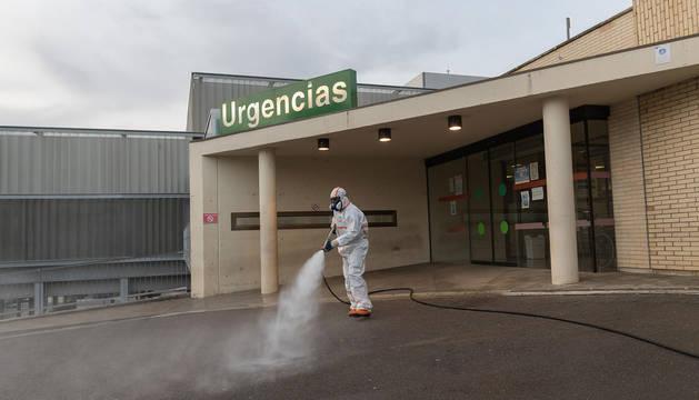 Un voluntario de Protección Civil fumiga los accesos al Hospital Reina Sofía.